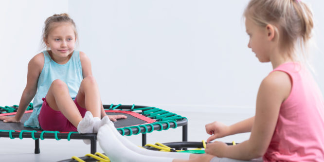 Two little girls sitting on trampolines in a very bright room, smiling at each other